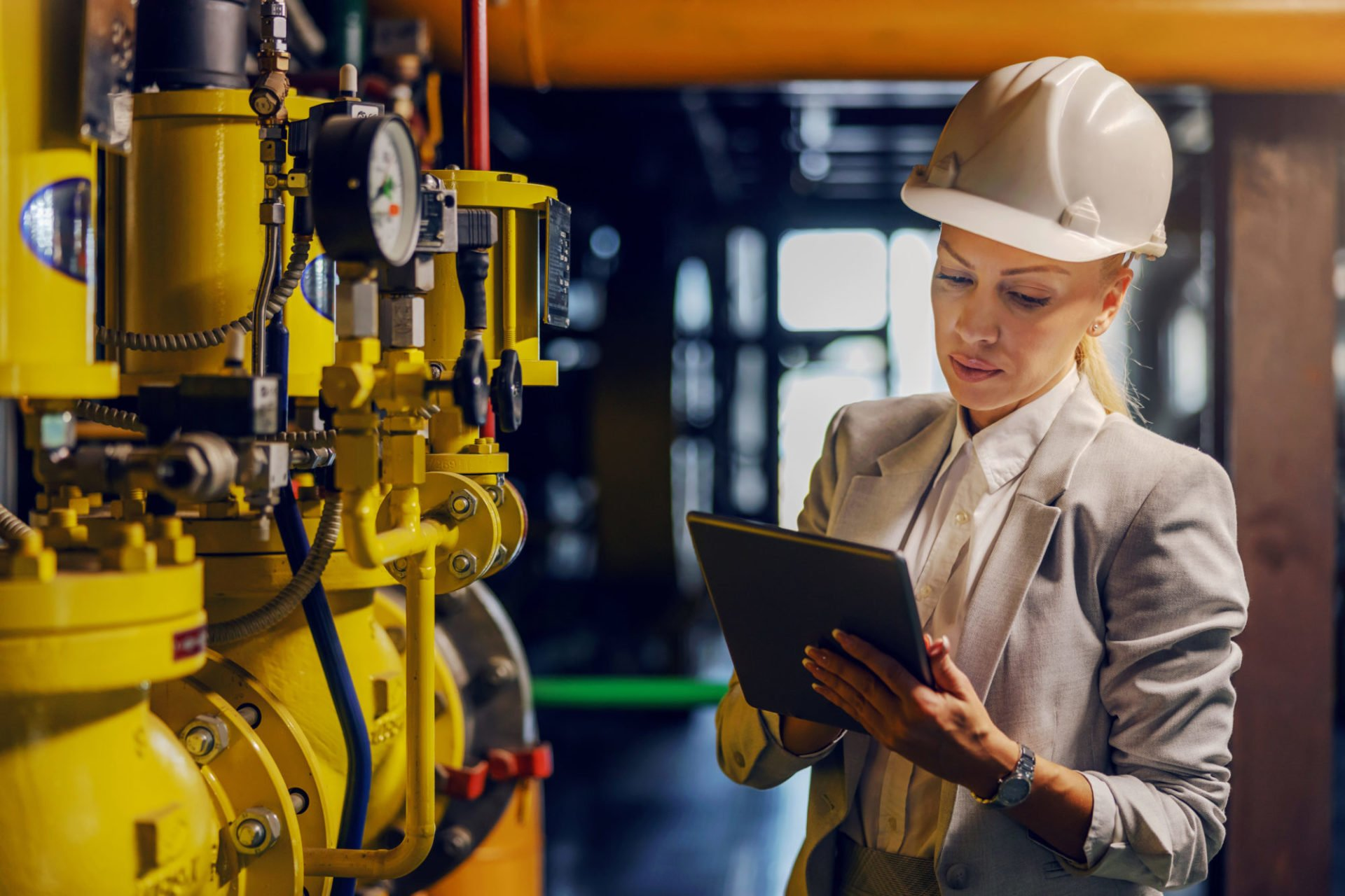 """""""Blond-dedicated-successful-businesswoman-in-forma-wear-checking-on-machinery-and-holding-tablet-while-standing-in-power-plant"""""""